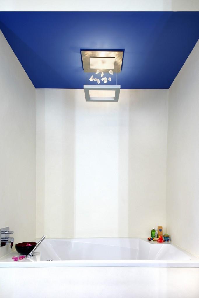 Überbreite Badewanne, Eingehüllt In Kalkpressputz Und Eine Abgehängte Decke  Mit Modernem Kronleuchter.
